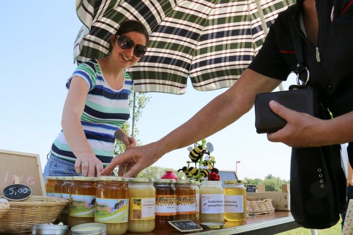 Caroline, de zus van Liesbeth verkoopt honing aan een bezoeker.